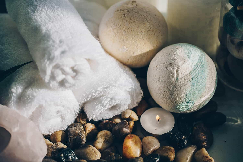Kerzen, nasse Steine, Badekugeln und Handtücher.